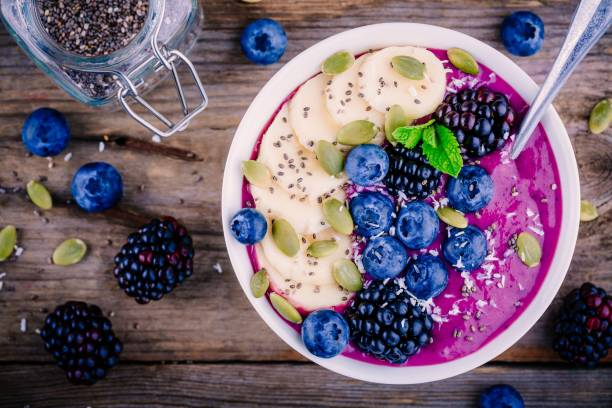 Smoothie bowl with fresh blackberries, blueberries, banana, sunflower seeds, pumpkin seeds, chia  seeds and coconut stock photo