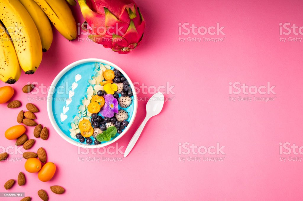 Smoothie bowl with fruits, berries, nuts and flowers on pink background. Tropical healthy smoothie dessert. Healthy breakfast, vegetarian food, lunch concept zbiór zdjęć royalty-free