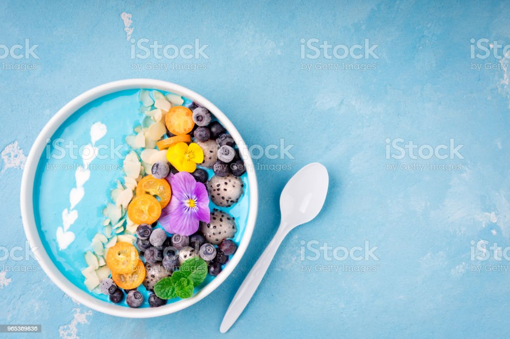 Smoothie bowl with fruits, berries, nuts and flowers. Tropical healthy smoothie dessert. Healthy breakfast, vegetarian, dieting concept stock photo