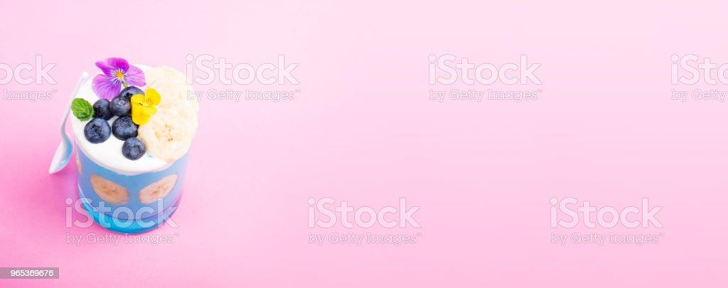 Dessert smoothie avec baies, noix, fruits et fleurs sur fond rose. Tropical smoothie sain. Petit-déjeuner sain, concept alimentaire végétarien - Photo de A la mode libre de droits