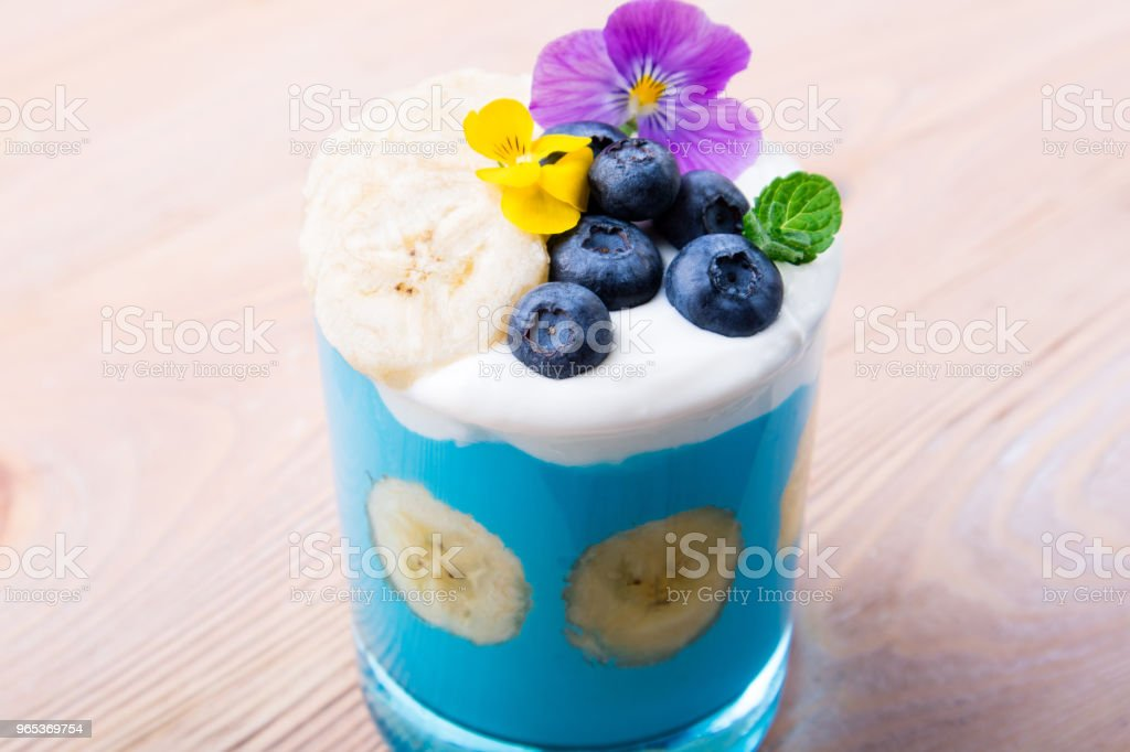 Smoothie dessert with fruits, berries, nuts and flowers on wooden background. Tropical healthy smoothie. Healthy breakfast, vegetarian food, lunch royalty-free stock photo