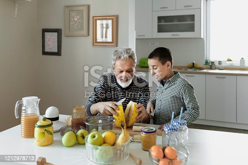 Grandfather and His Grandson Preparing Smoothie for a Healthy Breakfast at Home. The Concept of Healthy Eating and Dieting. Veggie Concept. Vegan. Healthy Eating is Important.