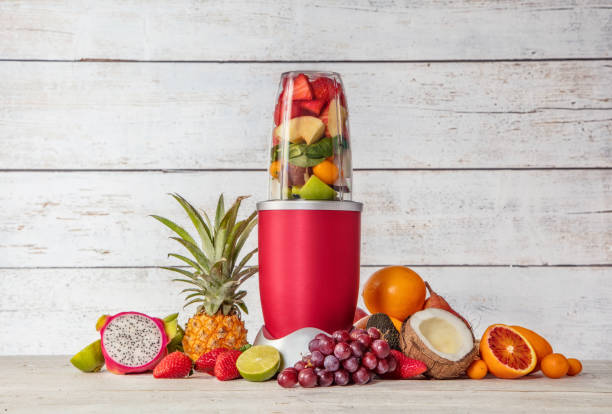 Smoothie maker mixer with pieces of fruit ingredients Smoothie maker mixer with pieces of fruit ingredients, placed in wooden interior. Healthy drink and lifestyle blender stock pictures, royalty-free photos & images