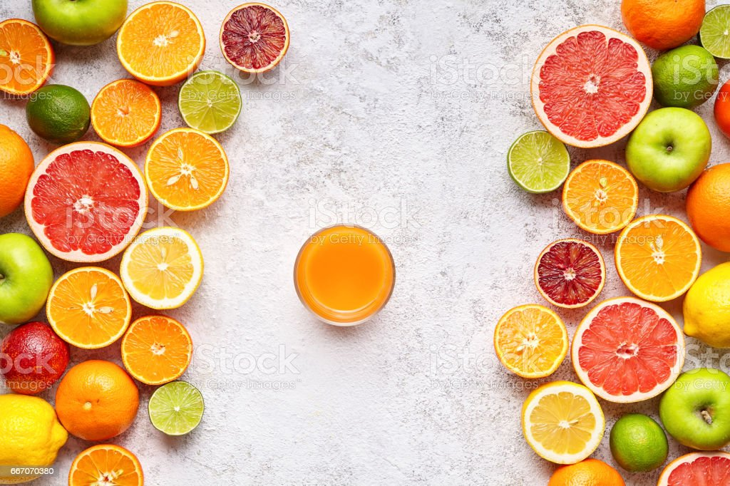 Smoothie or fresh juice in citrus fruits background flat lay, helthy vegetarian organic antioxidant detox diet stock photo