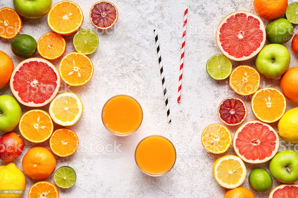 Smoothie or fresh juice vitamin c drink in citrus fruits background flat lay, helthy vegetarian organic antioxidant detox stock photo