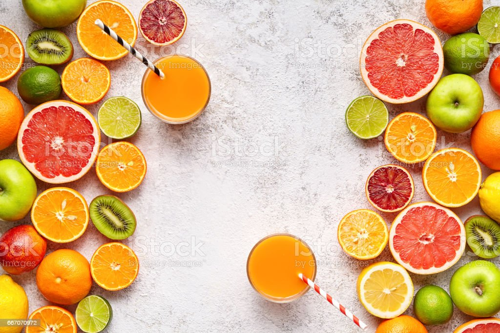 Smoothie or fresh juice vitamin c drink in citrus fruits background flat lay, helthy natural beverage stock photo