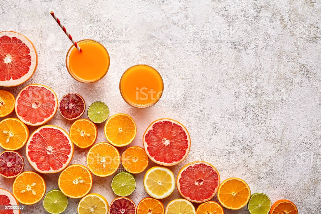 Smoothie or fresh juice vitamin in citrus fruits background flat lay, helthy beverage stock photo