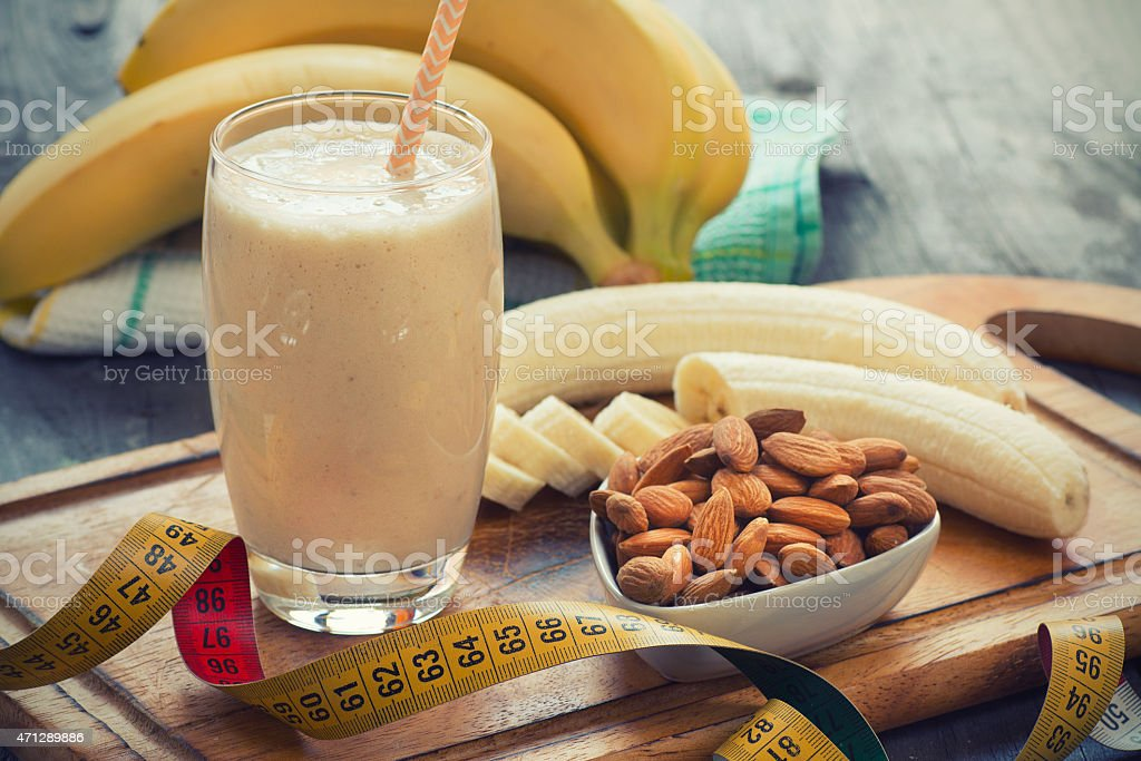 Smoothie with bananas and almonds next to measuring tape stock photo
