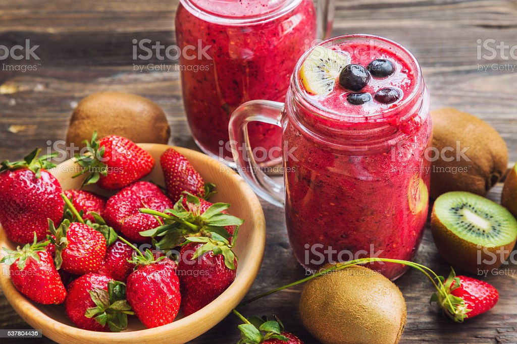 Smoothie with strawberries, kiwi and blueberries in jars stock photo