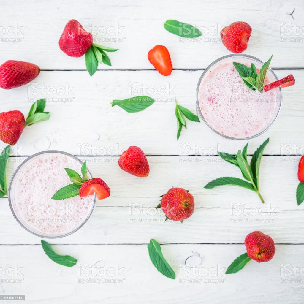 Smoothie with strawberry and pattern made of strawberries and mint leaves on white wood background. Fresh milkshake. Flat lay. Top view. royalty-free stock photo