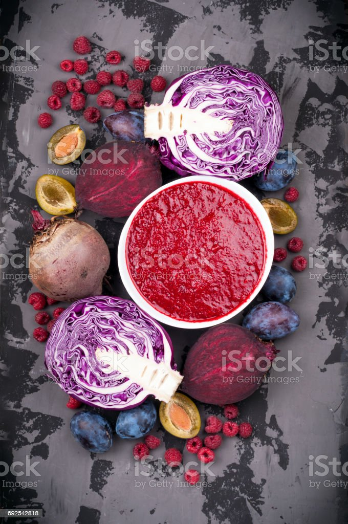 Smoothies bowl with purple fruit and vegetables on dark background. Healthy eating and diet concept. Top view stock photo