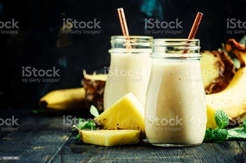 Smoothies from pineapple and banana in glass bottles stock photo