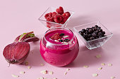 Vegetarian healthy smoothies from red berries and beetroot with almond plates in a glass cup on a pink paper background.