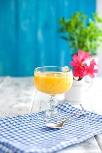 Foto de Batidos De Fruta Amarela Guardanapo Azul E Fundo De Madeira Flores Cor De Rosa Lugar Para Texto e mais fotos de stock de Abstrato