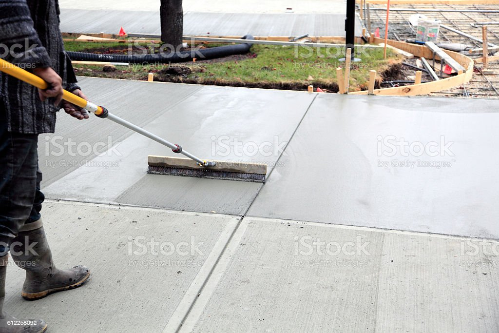 Smoothing And Finishing The New Concrete Driveway Stock