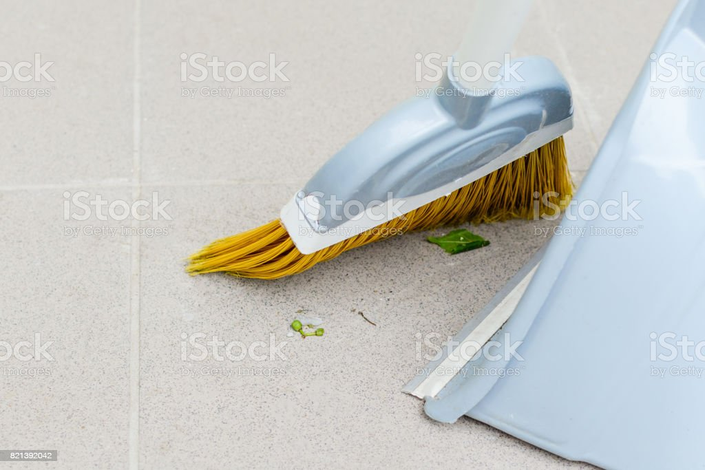 Smoothing on a tile with a broom to a bucket stock photo