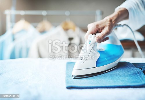 Closeup shot of an unidentifiable woman ironing clothes at home