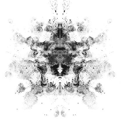 Smudged black eyeshadows in Rorschach inkblot patterns on a white background.