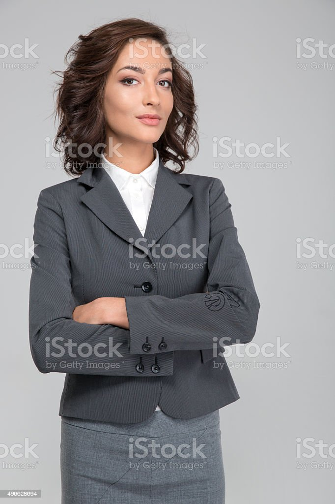 Smug young business woman with arms crossed stock photo