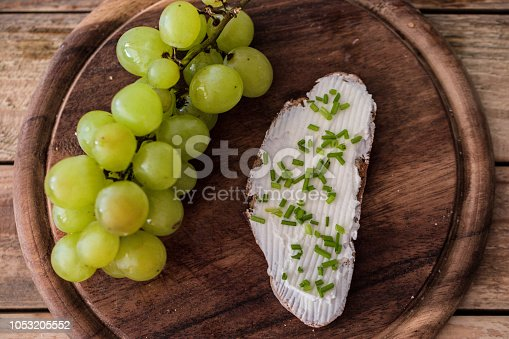 Simple breakfast, slices of rye bread with cow cheese cream spread with fresh white grape cluster at wood plate. Close up, selective focus