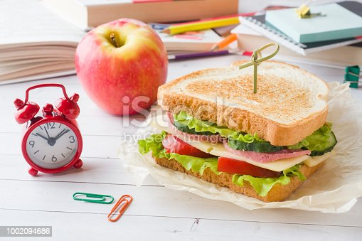istock Snack for school with sandwich, fresh Apple and orange juice. Colorful school supplies. 1002094686