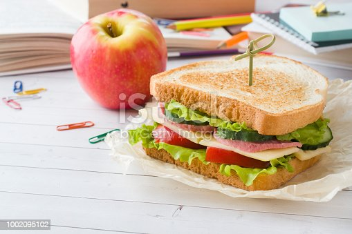 istock Snack for school with sandwich, fresh Apple and orange juice. Colorful school supplies. 1002095102