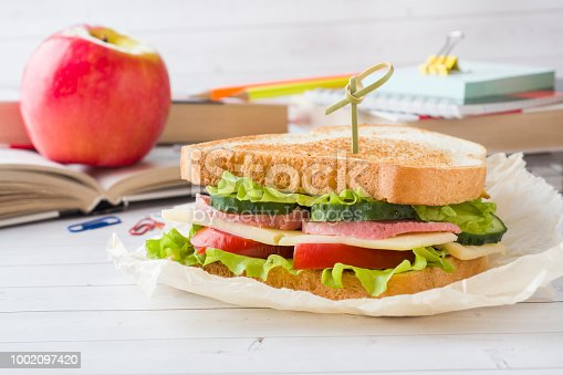istock Snack for school with sandwich, fresh Apple and orange juice. Colorful school supplies. 1002097420