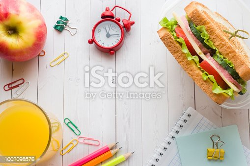 istock Snack for school with sandwich, fresh Apple and orange juice. Colorful school supplies. Copy space. 1002098576