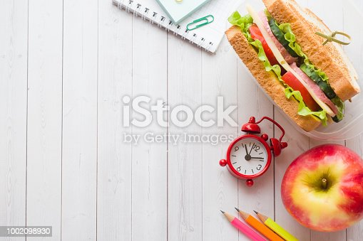 istock Snack for school with sandwich, fresh Apple and orange juice. Colorful school supplies. Copy space. 1002098930