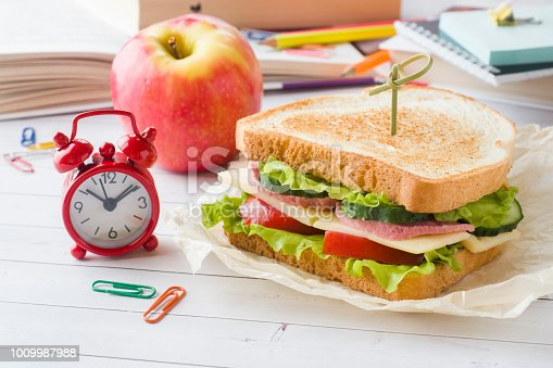 istock Snack for school with sandwich, fresh Apple and orange juice. Colorful school supplies. 1009987988
