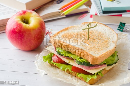 istock Snack for school with sandwich, fresh Apple and orange juice. Colorful school supplies. 1028199946