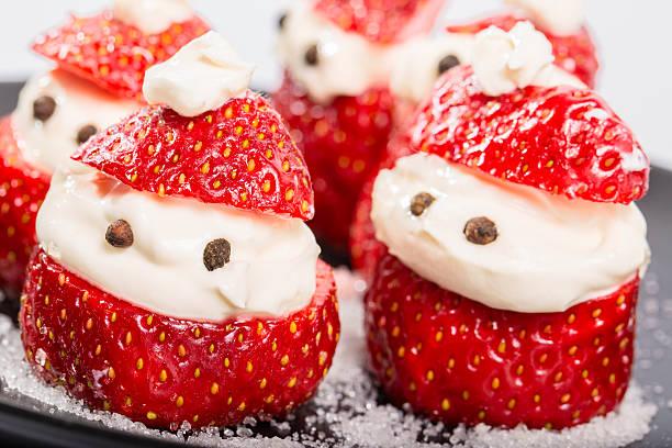 snack from strawberry and cream - weihnachtsmannhüte aus erdbeeren stock-fotos und bilder