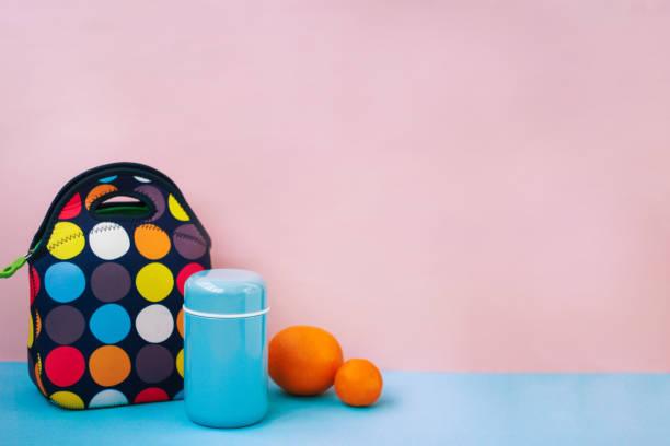 fika på en rast med en lunchbox. färgglad handväska, blå termos, apelsin, tangerin. plats för text, rosa bakgrund. - lunchlåda bildbanksfoton och bilder