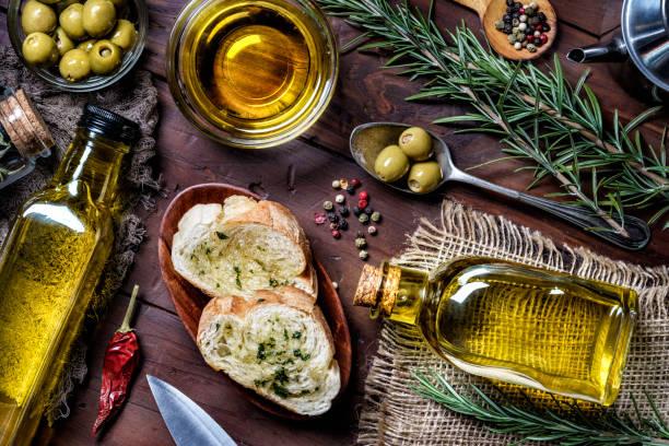 Snack ou apéritif de basilic à l'ail et bruschetta d'huile d'olive sur la table dans une cuisine rustique - Photo