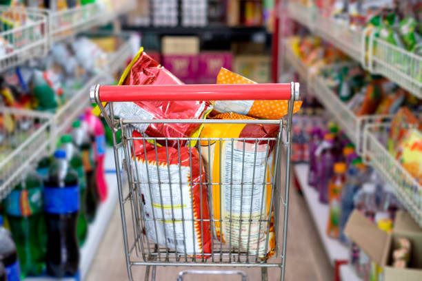 Snack packs in shopping cart at store stock photo