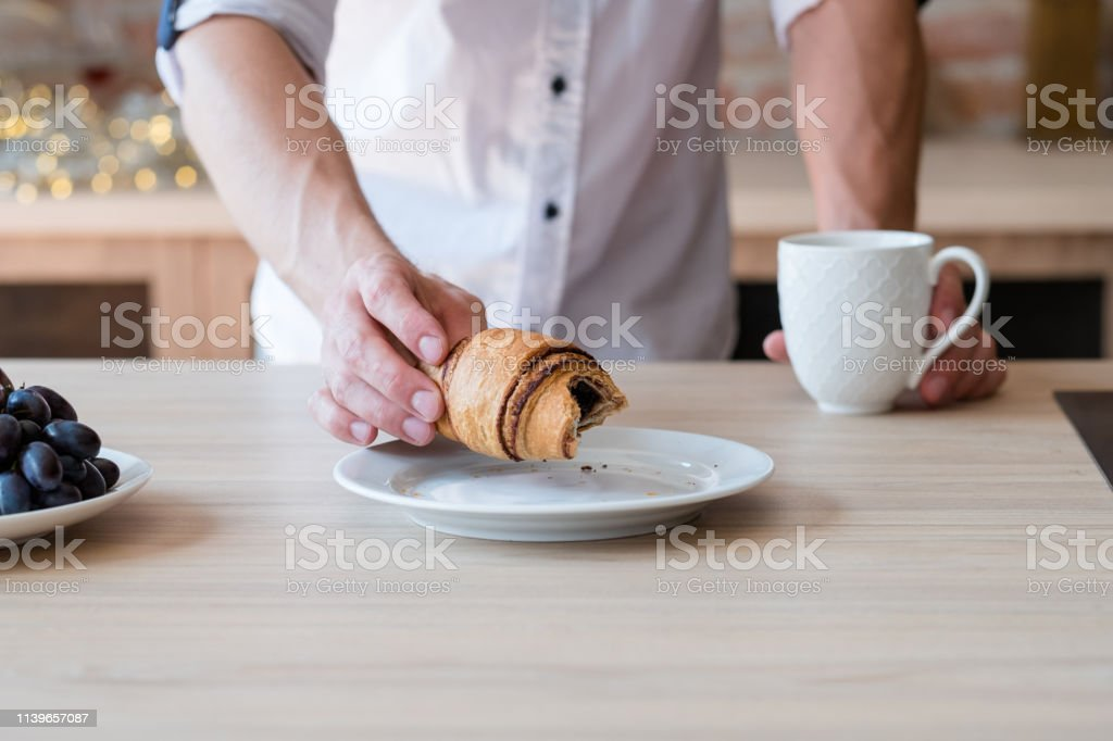 Daily snack. Pastry food habit. Man with cup of drink and croissant....