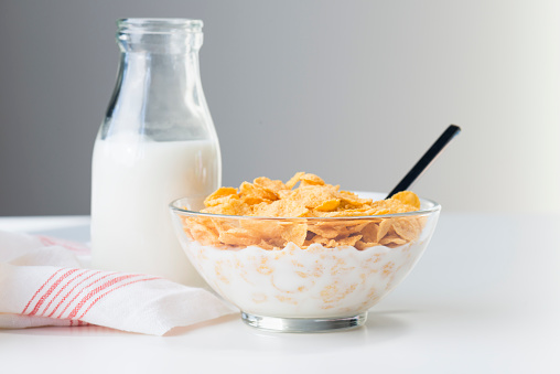 Bowl of corn flakes with milk and a bottle of milk on white background.