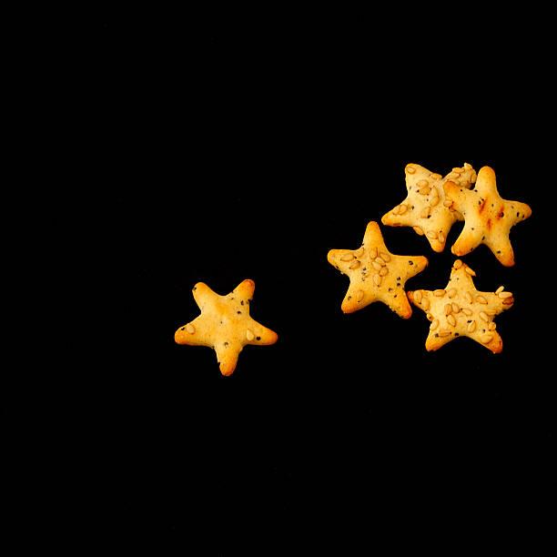 snack salati a forma di stella, formato quadrato snack salati a forma di stella, su fondo nero, formato quadrato quadrato stock pictures, royalty-free photos & images
