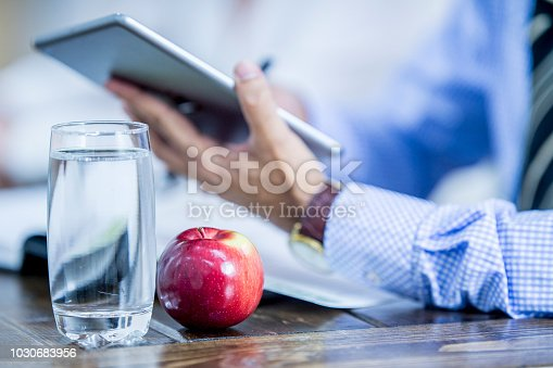 An apple and glass of water are on top of a desk. An office worker is using a tablet computer.