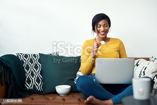 Cropped shot of an attractive young woman sitting on her sofa and eating potato crisps while using her laptop