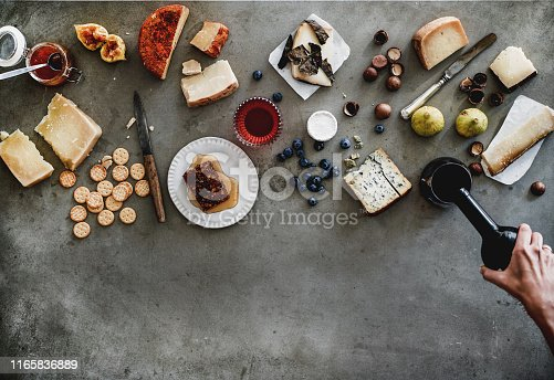Wine snack variety. Flat-lay of cheeses, honey, fruit, nuts, crackers, female hands pouring wine from bottle to glass over grey concrete background, top view, copy space. Gathering, party food concept