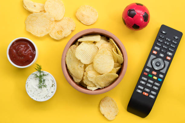 snacks for watching tv on yellow background top view mock-up.the concept of tv viewing and sports tournaments. - telecomando background foto e immagini stock