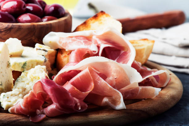 Snacks or antipasti, crostini, prosciutto, blue cheese and olives stock photo