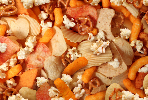 Snacks background with salty crunchy treats as potato chips and cheese flavored puffs fried or baked food as pretzels pop corn and nachos as a symbol of assorted party mix appetizer.
