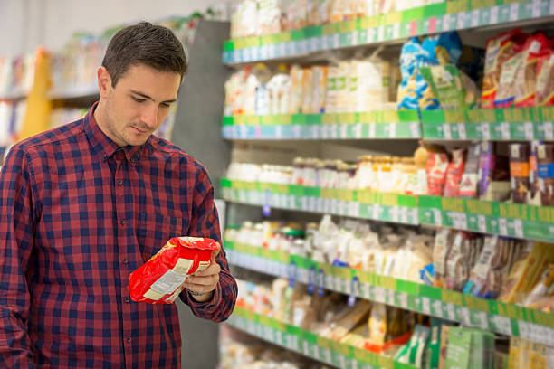 Snacks shopping Man choosing snacks in supermarket snack aisle stock pictures, royalty-free photos & images