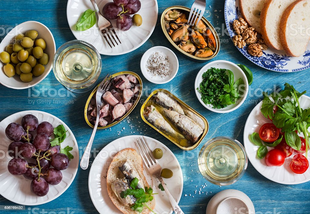 Snacks table - canned sardines, mussels, octopus, grape, olives, tomato stock photo