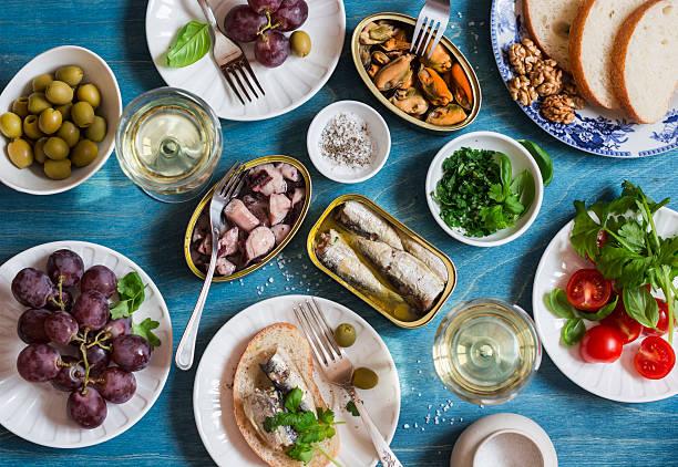 snacks table - canned sardines, mussels, octopus, grape, olives, tomato - mediterranean food imagens e fotografias de stock