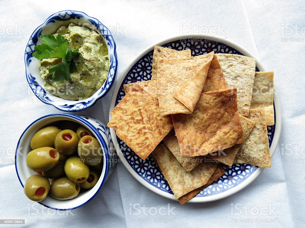 Snacks with hummus, chips and olives stock photo