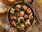 'Escargot in a Herb Butter, White Wine and Garlic Sauce with Fresh Parsley and Crusty French Bread -Photographed on Hasselblad H3D2-39mb Camera'