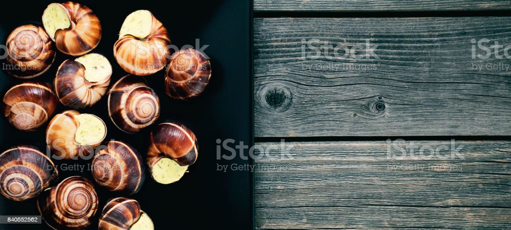 Snails on a dark plate on a wooden table. Panorama. French dish. stock photo